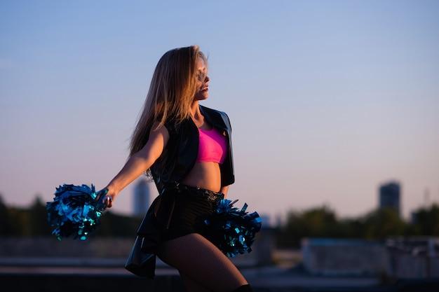 Cheerleader mit pompons bei sonnenuntergang im freien auf dem dach tanzen