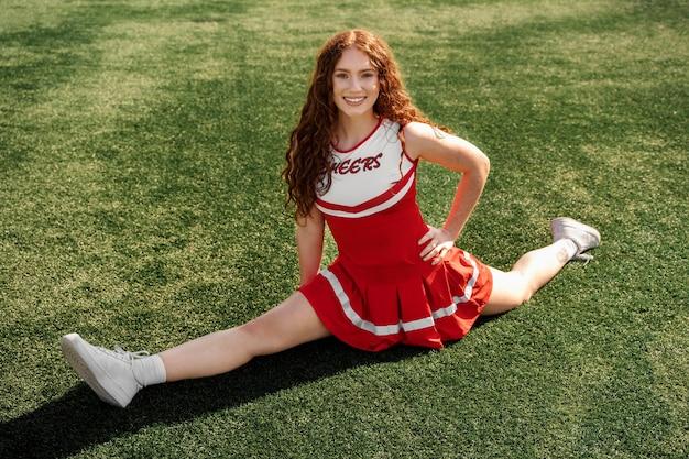 Cheerleader mit vollem schuss beim spagat
