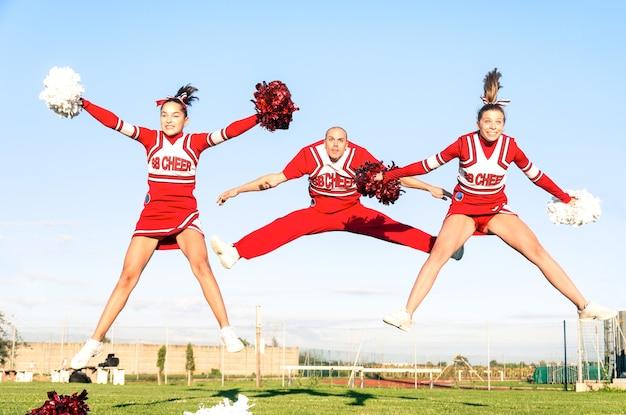 Cheerleader-team mit männlichem trainer, der einen synchronisierten sprung durchführt