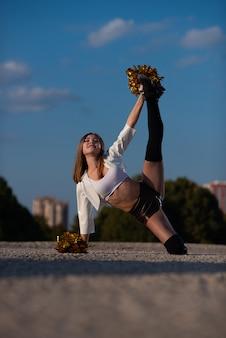 Cheerleadermädchen mit den pompoms, die draußen tanzen