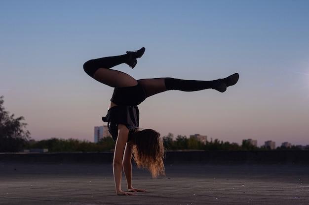Cheerleadermädchen mit pompons führt akrobatisches element draußen auf dem dach durch