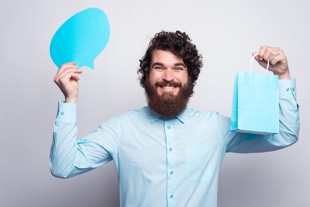 Cheerul junger mann im blauen hemd, das sprechblase und einkaufstasche hält.