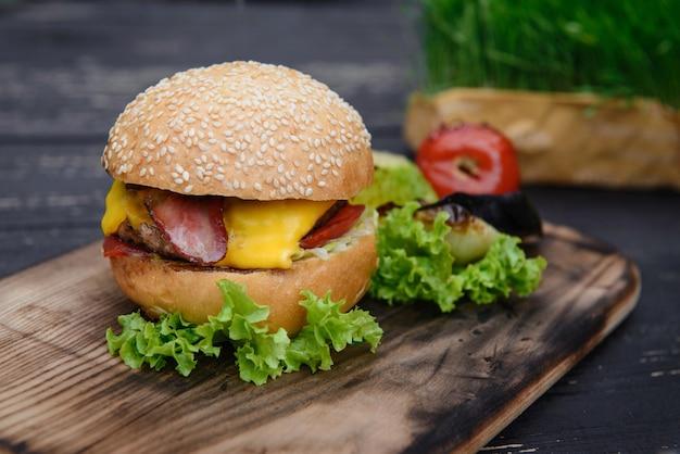 Cheeseburger auf dem holztisch im freien, serviert mit gegrilltem gemüse