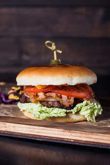 Cheeseburger auf einem holztablett in einem restaurant, auf einem dunklen hintergrund.