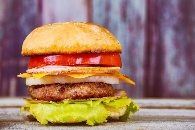 Cheeseburger auf rindfleischpasteten und frischen salatbestandteilen gedient mit auf einer rustikalen hölzernen tabelle