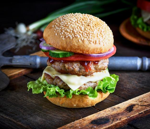 Cheeseburger in einem brötchen mit sesam, in der mitte frischem gemüse und fleisch schnitzel