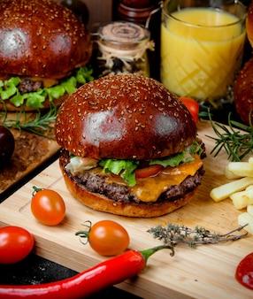 Cheeseburger in weichem brot und pommes auf einem holzbrett