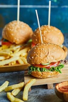 Cheeseburger mit bratkartoffel auf dem holzbrett