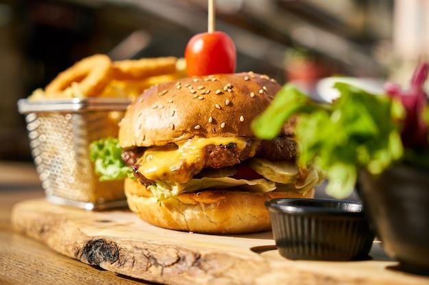 Cheeseburger mit pommes-frites auf dem holztisch