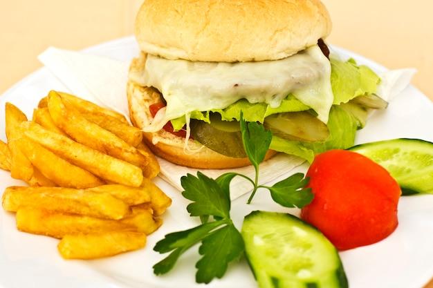 Cheeseburger mit pommes frites, gurkenscheiben und tomaten