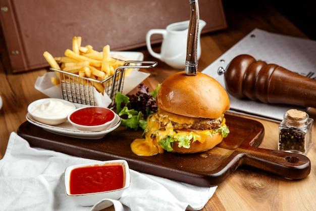 Cheeseburger mit pommes frites ketchup und mayo an bord