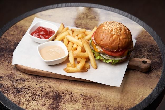Cheeseburger mit pommes und saucen. frischer burger und pommes frites auf holzschneidebrett. fast food, junk food