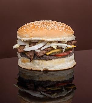 Cheeseburger mit schnitzel und fleisch auf dunklem hintergrund mit reflexionsnahaufnahme