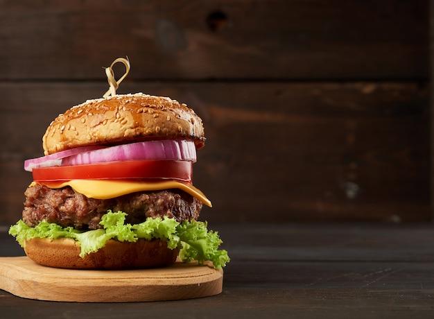 Cheeseburger mit tomaten, zwiebeln, grillkotelett und sesambrötchen auf einem alten hölzernen schneidebrett, brauner hintergrund. fast food, kopierplatz