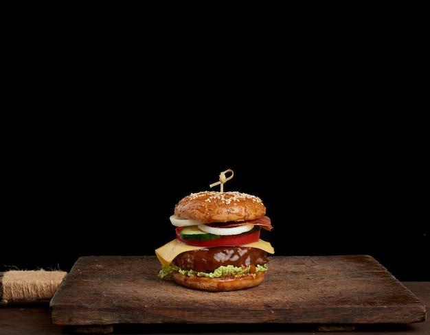 Cheeseburger mit tomaten, zwiebeln, grillkotelett und sesambrötchen auf einem alten holzschneidebrett