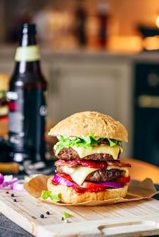 Cheeseburger mit zwei rindfleisch-pastetchen cheddar-käse-speck-eisbergsalat geschnittene tomaten und rote zwiebel
