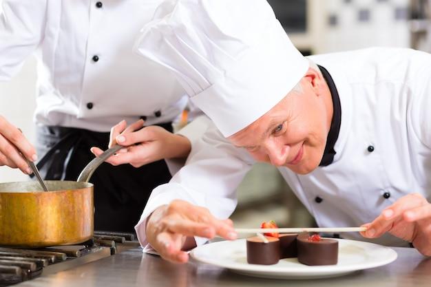 Chef als patissier, der im restaurantnachtisch kocht