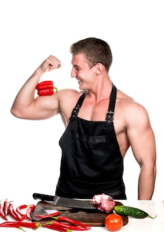 Chef bodybuilder lacht beim zubereiten eines abendessens mit gemüse und fleisch.
