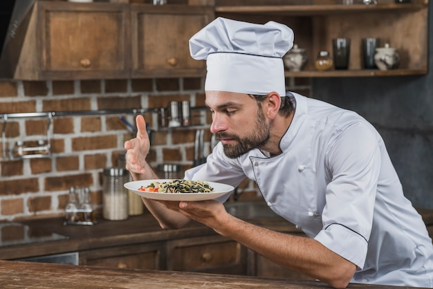 Chef, der das aroma des tellers in der küche riecht