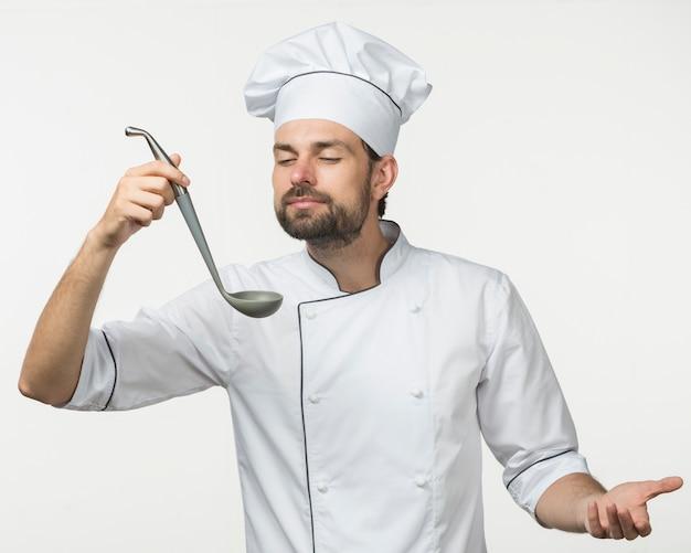Chef, der den geruch der suppe in der schöpfkelle genießt