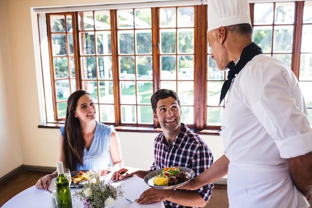 Chef, der den jungen paaren lebensmittel sitzt in einem restaurant dient