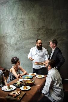 Chef, der den kunden im restaurant lebensmittel präsentiert