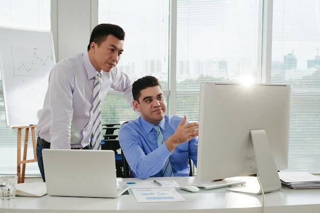 Chef, der die arbeit überprüft, die von seinem untergebenen erledigt wird, der die ergebnisse auf dem computerbildschirm zeigt
