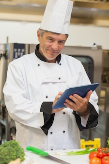 Chef, der digitale tablette und das lächeln verwendet