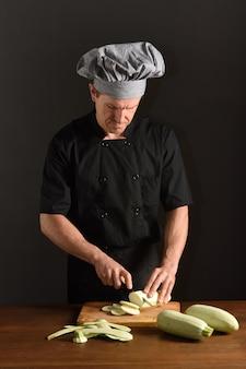 Chef, der eine zucchini schneidet