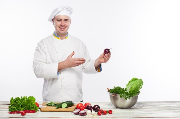 Chef, der frischgemüsesalat in seiner küche kocht