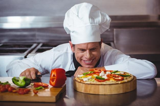 Chef, der gemüse schneidet, um eine pizza anzuziehen