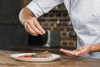 Chef, der Gewürze über dem vorbereiteten Teller besprüht