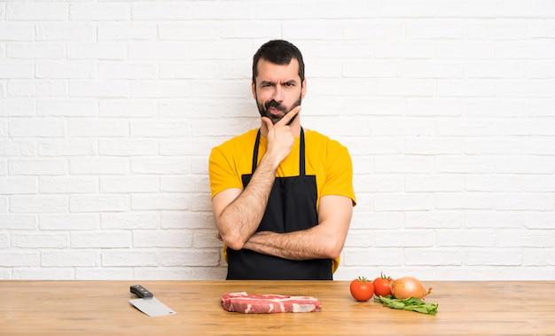 Chef, der in einem küchendenken hält