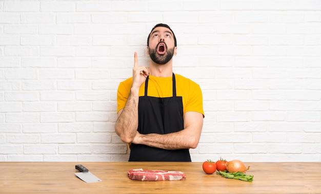 Chef, der in einer küche oben zeigt und überrascht hält