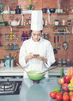 Chef der jungen frau betrachten den smartphone am küchenraum