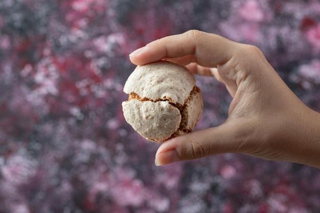 Chef, der knusprige kekse mit zuckerpulver in der hand hält.