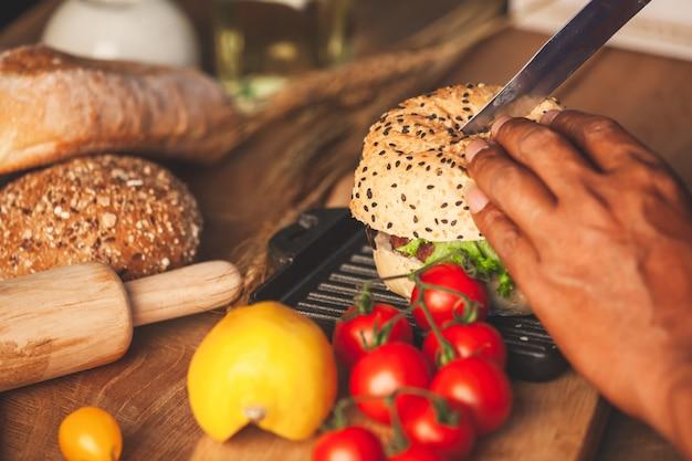 Chef, der köstlichen selbst gemachten hamburger mit frischgemüse in der küche kocht und schneidet