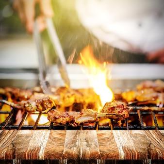 Chef, der lammrippen auf heißer flamme, grill kocht im abend und sonnenuntergang mit hölzernem grillt