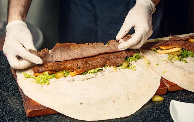 Chef, der lavash döner mit fleisch und gemüse zubereitet.