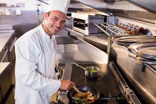 Chef, der lebensmittel in der küche zubereitet