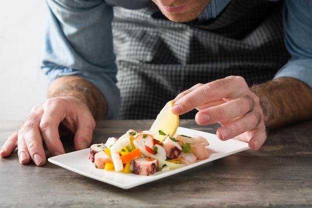Chef, der meeresfrüchte ceviche auf holztisch zubereitet