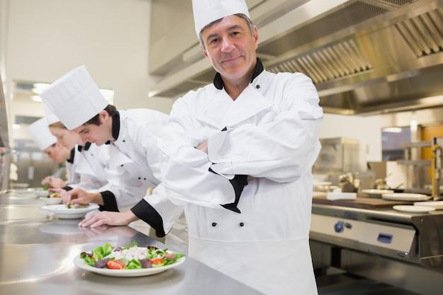 Chef, der mit anderen bereitet salate zubereitet