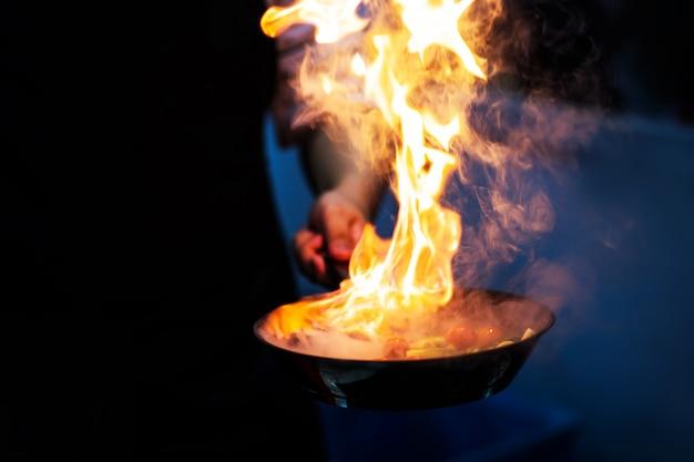Chef, der mit flamme in einer bratpfanne auf einem küchenherd kocht