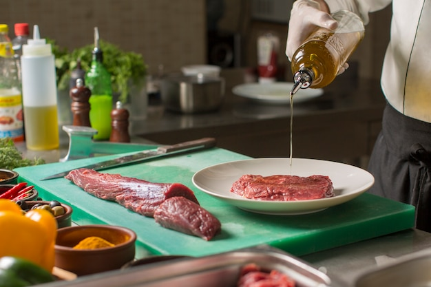 Chef, der olivenöl von der flasche auf steakstück in der platte gießt