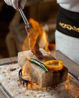 Chef, der rindfleischsteakstück mit klipp auf steinziegelstein auf feuer kocht