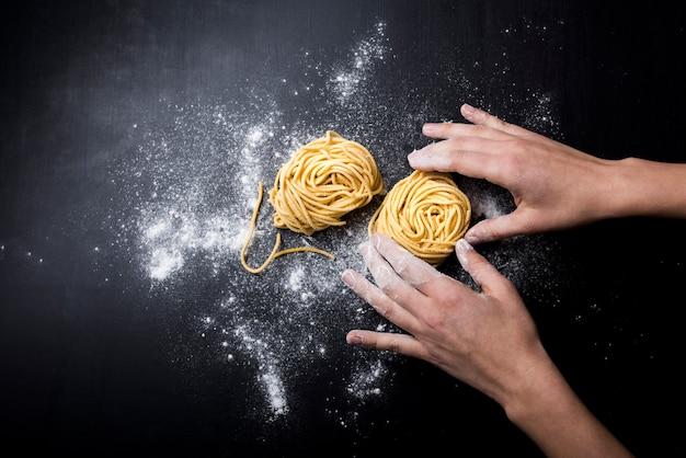 Chef, der selbst gemachtes italienisches bandnudelnnest auf küchenarbeitsplatte vorbereitet