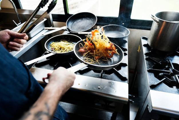 Chef, der spagetti in der küche kocht