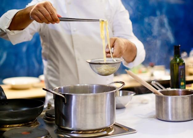 Chef, der spaghettis in der küche kocht