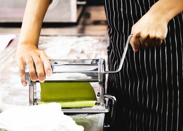 Chef, der teig für gebäck, frische teigwaren und teigwarenmaschine auf küche macht