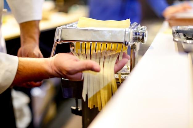 Chef, der teigwaren mit einer maschine, hausgemachte frische teigwaren macht